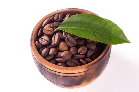wooden bowl with coffee beans and leaf