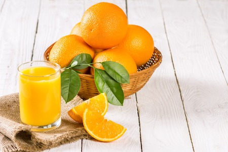 ascorbic acid: oranges and a glass of fresh juice on a wooden table