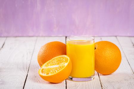 ascorbic acid: glass of juice and orange slices on a table Stock Photo