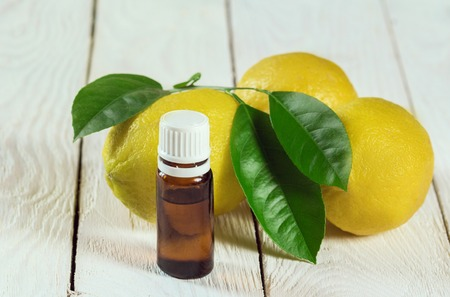 fresh lemon and essential oil on wooden table
