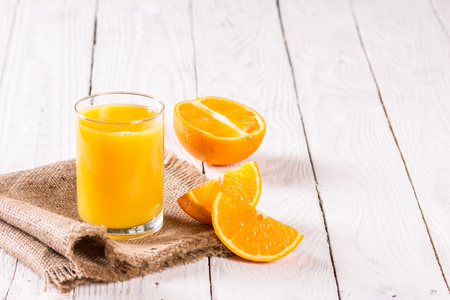 oranges and a glass of fresh juice on a wooden table