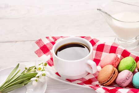 Beautiful delicious almond on a plate with snowdrops and a cup of coffee on a wooden table