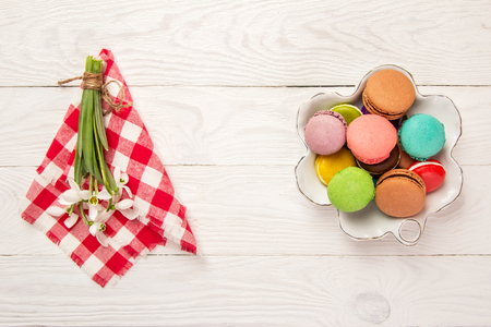 Colorful macaroons on a plate with snowdrops Stock Photo