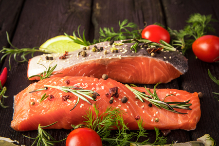 pickling: marinated salmon with spices, tomatoes and lemon Stock Photo