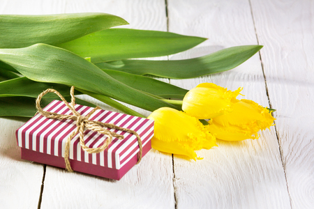 Bouquet of beautiful tulips. Gift box on a white wooden background