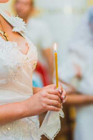 christian marriage: The groom and the bride with candle. Wedding ceremony in church
