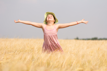Happy little girl playing in the wheat