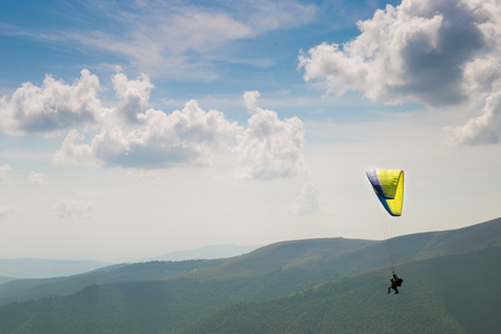 paraglider flies. paraglider over the tops of the mountains in summer sunny day. Stock Photo