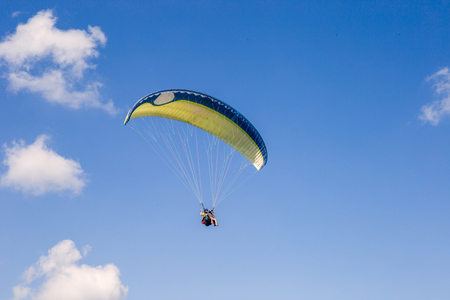 paraglider flies. paraglider over the tops of the mountains in summer sunny day. 写真素材