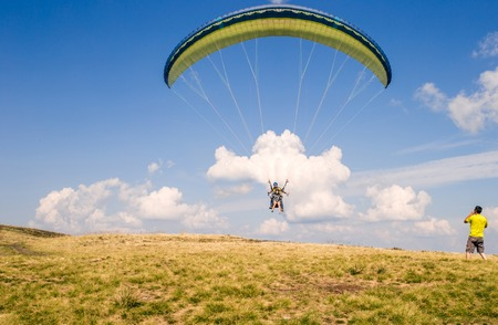 paraglider flies. paraglider over the tops of the mountains in summer sunny day. Фото со стока