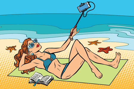 Beautiful young woman on the beach doing a selfie