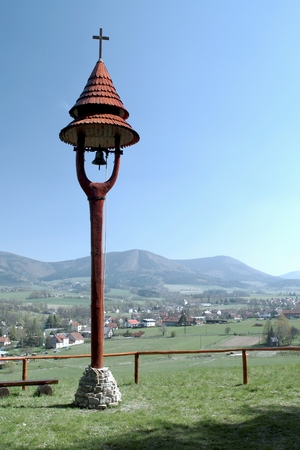 Small wooden belfry with the Beskydy mountains in the background