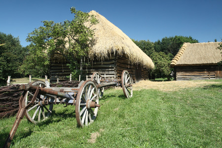 Old wooden cart in front of an old timbered barn in the Museum of the Villages of Southeast Moravia in Straznice (Slovacko region), Czech Republic. The open - air museum (opened in 1981) includes the folk architecture of South Moravia, especiall rural far Stock Photo