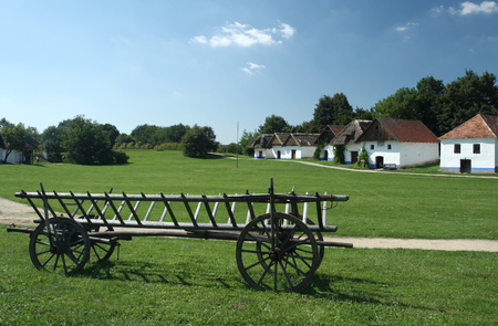 An old hay wagon with a traditional Moravian viticulture buildings in the background.