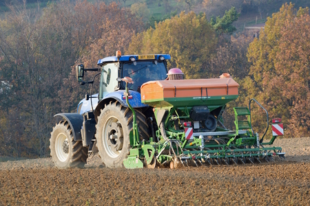 A modern tractor with a sowing machine when planting crops in a rural field