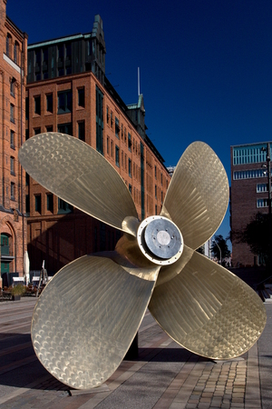 Giant four-blade ship propeller in front of the International Maritime Museum in Hamburgs Speicherstadt district. Stock Photo