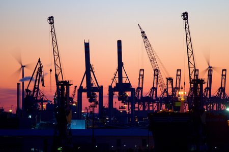 Silhouette of container of gantry cranes in the harbor of Hamburg, Germany at sunset.