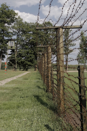 Barbed wire fence with watchtower in background Grutas Park near Druskininkai, Lithuania Stock Photo