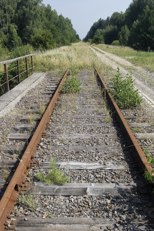 An old abandoned railway line with rusty tracks and sleepers overgrown with grass. Stock Photo