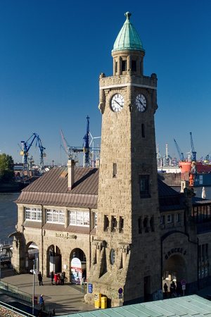 Clock Tower of the famous Hamburger Landungsbruecken with a commercial harbor and Elbe river, St. Petersburg. Pauli district, Hamburg.