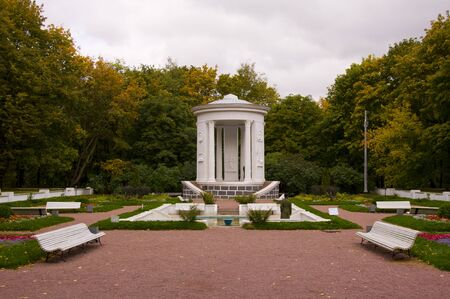 A fountain and a gazebo in the autumn park