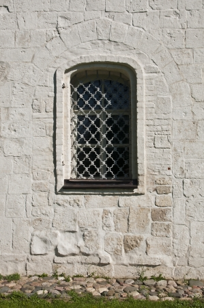 An old window at the white stone wall photo