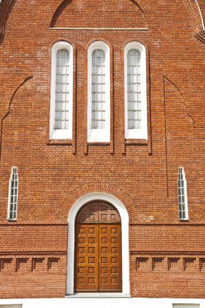 The wall of the church with the door of the red brick photo