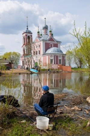 water s edge: pesca presso il laghetto sullo sfondo della Chiesa russa Archivio Fotografico