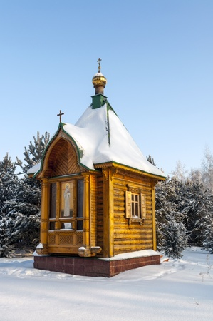 Traditional wooden church in winter forest photo