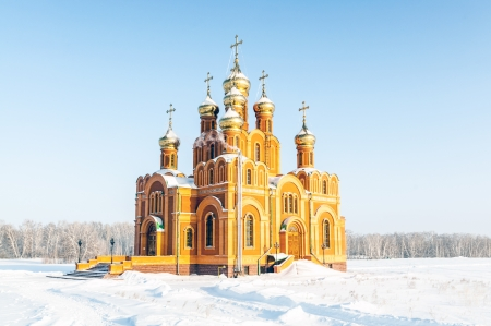 An old orthodox church in snowy winter field photo