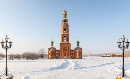 An old orthodox church in winter in a snowy field photo