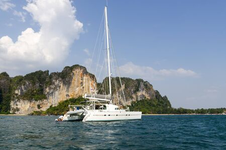 Yacht in the sea against the cliffs in Krabi Thailand photo