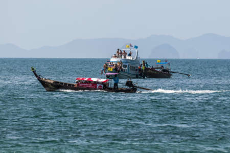 Traditional Thai boat floats on the high seas with tourists