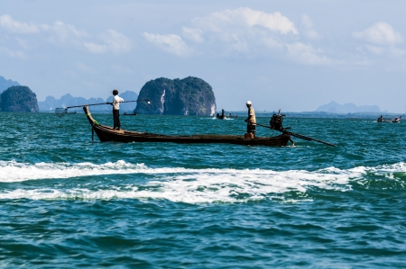 Traditional fishing boat with fishermen on the high seas against the background of the islands in Thailand