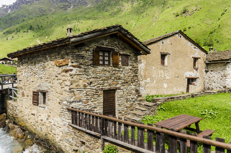 Stone shepherd s house in a peasant village in alpine meadows surrounded by mountains  Northern Italy