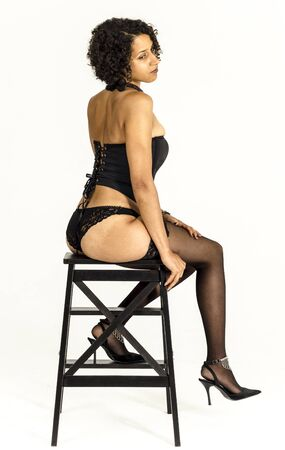Young mulatto woman in black lingerie and stockings