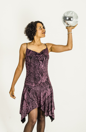 Mulatto girl in a cocktail dress with a disco ball