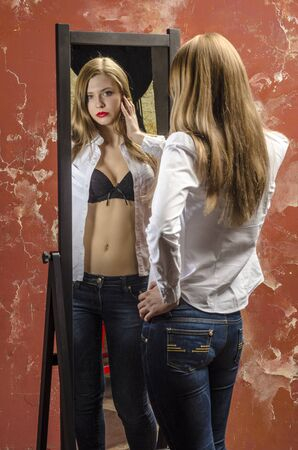 Beautiful girl in unbuttoned white shirt and jeans look at mirror