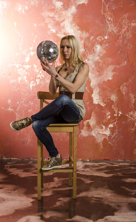 The girl the blonde in jeans and shirt with a disco mirror ball
