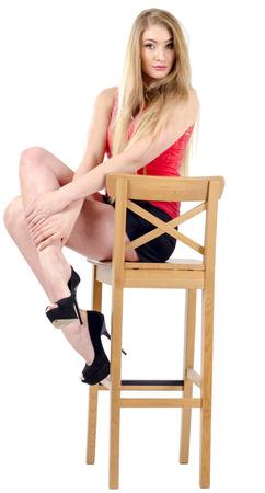 falda corta: alegre ni�a de pelo largo hermosa en una falda corta que se sienta en una silla y hacer gestos