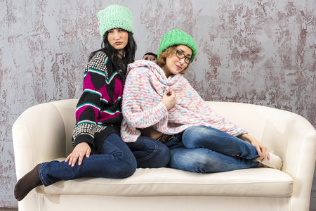 Two young girls friends sitting on a couch in the woolen clothes Stock Photo