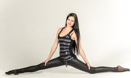 chica gimnasta delgada morena en una blusa negro y medias con brillo