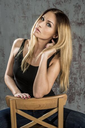 Beautiful slim blonde in jeans and a black T-shirt Stock Photo