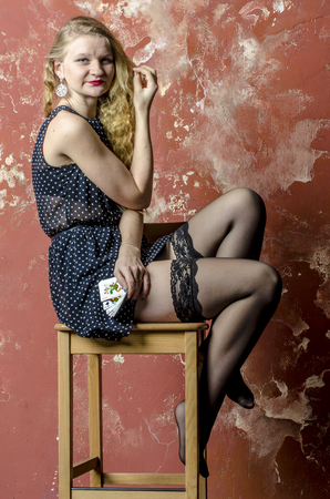 one girl only: Young girl with blonde curly hair in a long dress with polka dots and stockings with playing cards Stock Photo