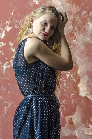 Young blonde girl with curly long hair in a polka-dot dress
