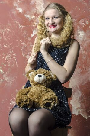Young blonde girl with curly long hair in a polka-dot dress with teddy bear Stock Photo