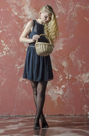 Young girl with blonde curly hair in a long dress with polka dots and stockings dancing with a basket