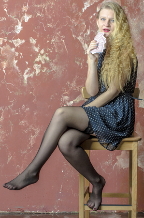 Young girl with blonde curly hair in a long dress with polka dots and stockings with playing cards 스톡 콘텐츠