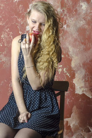one girl only: Young blonde girl with curly long hair in a polka-dot dress eating an apple