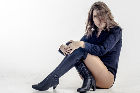 Haired girl in a dark blue shirt and high boots on high heels Reklamní fotografie